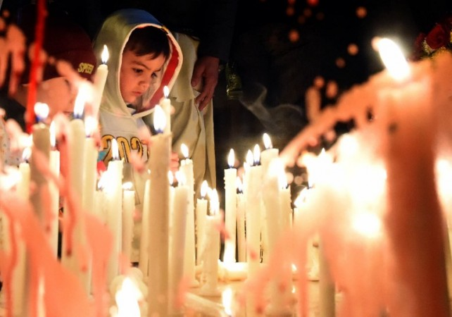 Pakistani civil society activists light candles in Quetta on December 16, 2015, on the first anniversary of attack on Army Public School Peshawar. Pakistan's leader, speaking beneath portraits of children killed by Taliban bullets, called for vengeance as the country marked the first anniversary of a school massacre that killed 151 people in its worst-ever extremist attack. AFP PHOTO / Banaras KHAN / AFP PHOTO / BANARAS KHAN