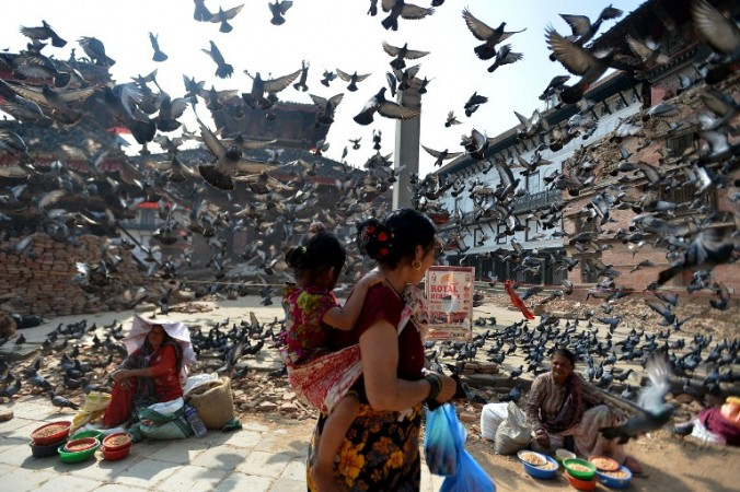 Flying pigeons pass over Nepalese street vendors near the earthquake damaged UNESCO World Heritage Site, Durbar Square in Kathmandu on May 20, 2015. Nearly 8,500 people have now been confirmed dead in the disaster, which destroyed more than half a million homes and left huge numbers of people without shelter with just weeks to go until the monsoon rains. AFP PHOTO / ISHARA S. KODIKARA / AFP PHOTO / Ishara S.KODIKARA